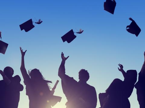 Students throw their graduating hats into the air