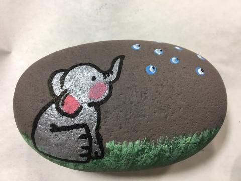 A rock painted with an elephant sitting on grass.