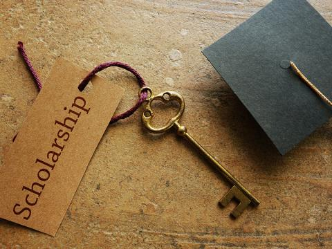 A golden key with a tag that says scholarship is placed next to a graduation hat on a wood table