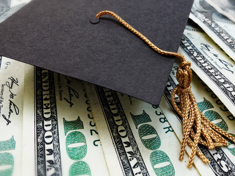 A black graduation hat with gold tassels sits on top of several one-hundred dollar bills.