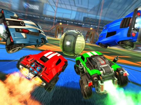 Four cars from Rocket League race to hit the soccer ball into the goal