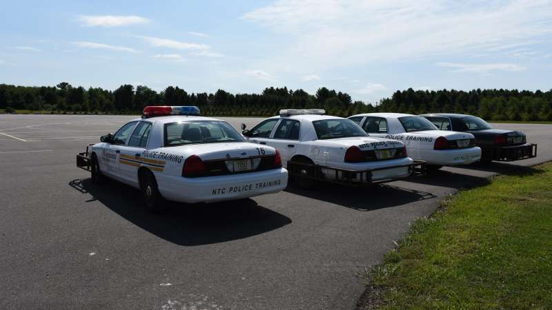 Four NTC police training vehicles parked in the practice area