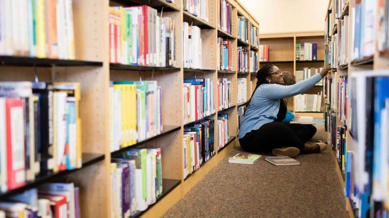 Students in the library searching for books