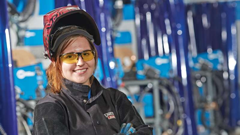 Welding student with her mask lifted over her head posing for portrait
