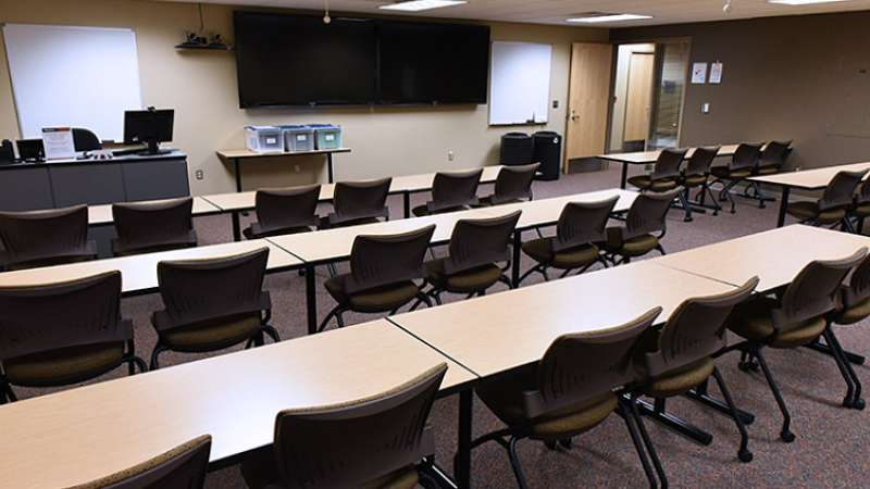 A training room with conference tables and chairs, as seen from the back of the room.