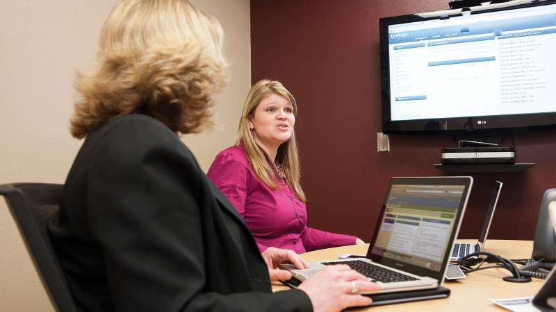 Two financial advisors sit next to each other in an office going over finanical information displayed on an overhead monitor