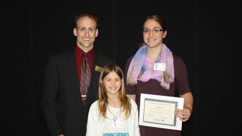 Brad Gast stands next to a student who received the Scott and Lucas Gast Scholarship. A young girl stands in front of them.