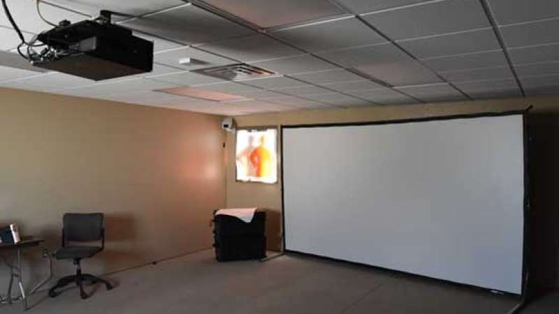 Indoor shooting simulator using a projector and large screen mounted to one wall in a classroom.