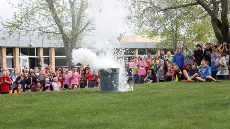 A large group of kids watch a science experiment in the courtyard at the NTC Wausau campus.
