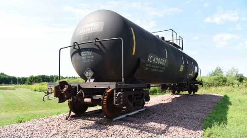 An oil tanker railcar sits in a gravel area.
