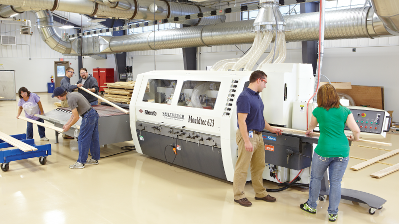 Two students are operating a Moulder