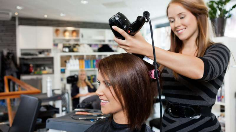 A cosmetologist styles her client's hair.