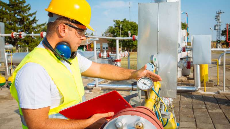 A gas utility worker checks the pressure of a system.
