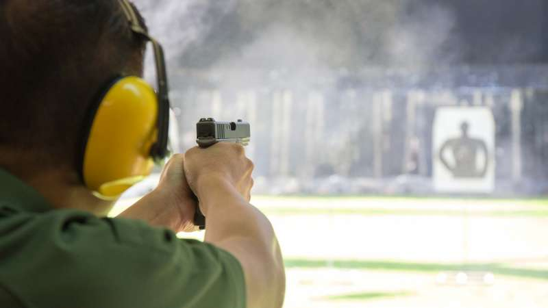 A man wearing ear protection points his gun at a target in the background.