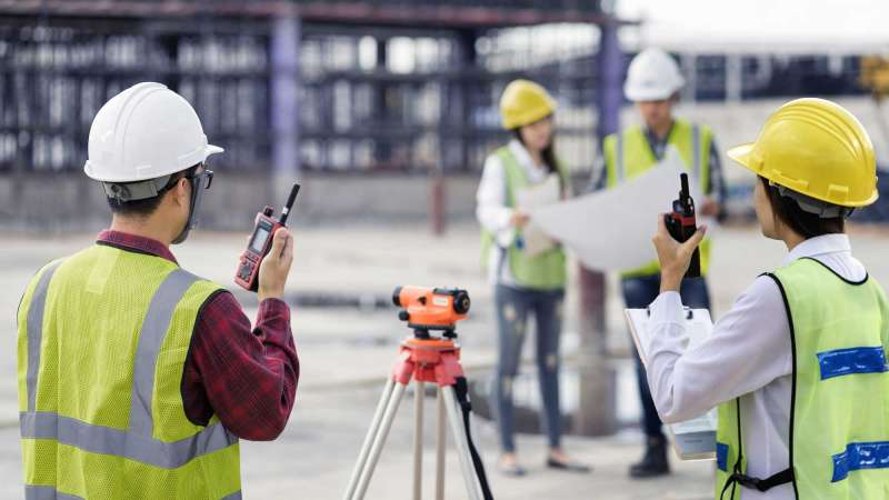 A crew standing at a worksite, examining blueprints and communicating via walkie talkies.