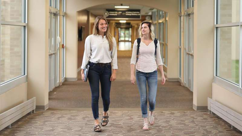 Two students walking down a hallway of the Wausau Campus, one carrying books, the other with a backpack on.