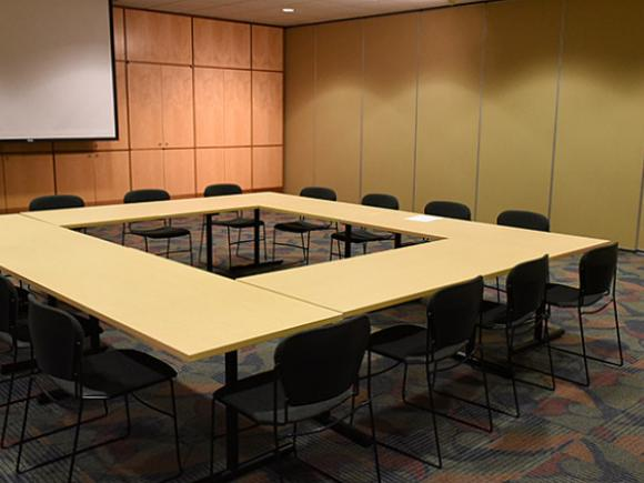 A large training room with the wall closed, dividing the training room into two. Tables are set up in a square pattern, with 4 chairs on each side.