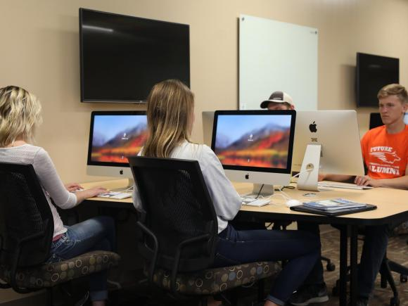 Four students sit down at iMacs, getting ready to log in.