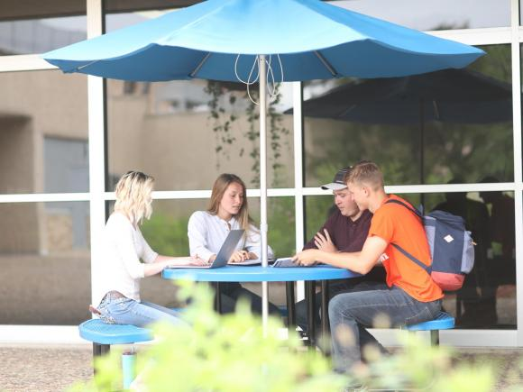 Four students sitting at a picnic table in the courtyard of the Wausau campus.