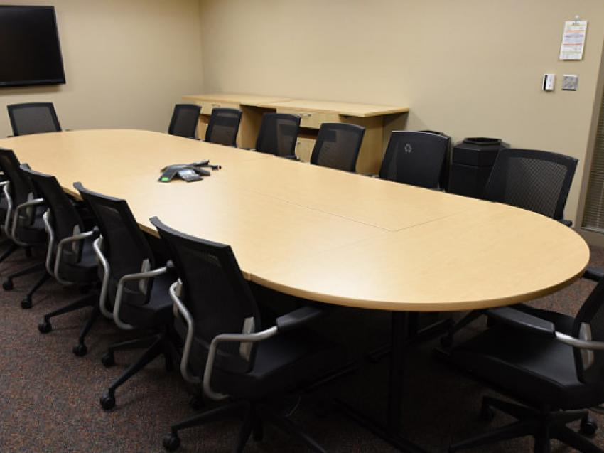 A conference room with one table lined by conference chairs on each side and at the ends.