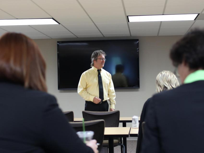 Business instructor teaching business people.