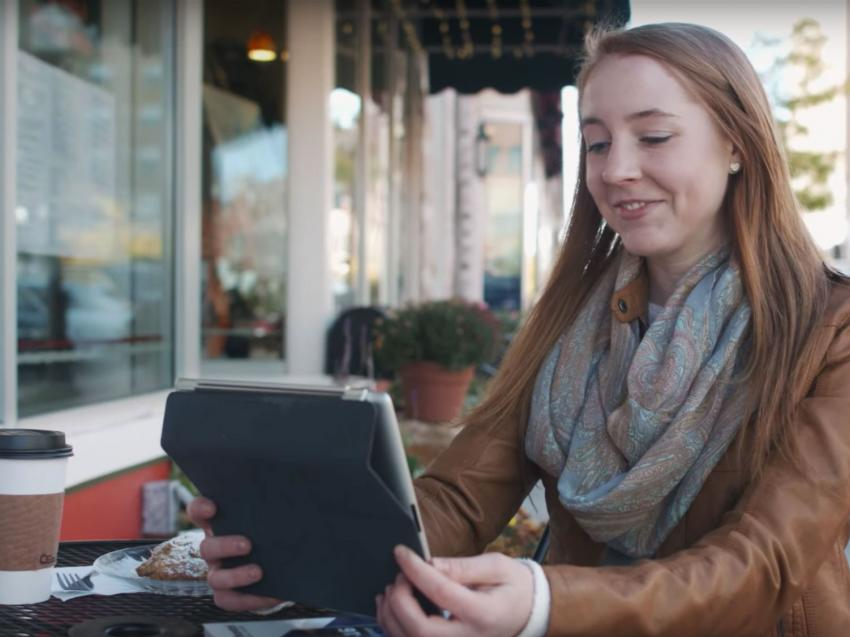 Virtual College student doing classwork outside of a cafe.