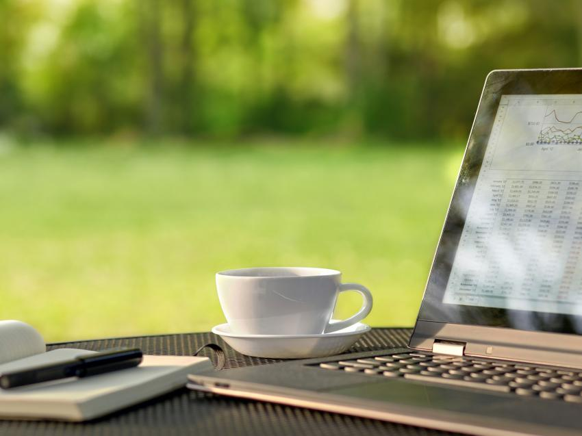 A close up view of a laptop, notebook, and a cup of coffee on a table outside near grass and trees