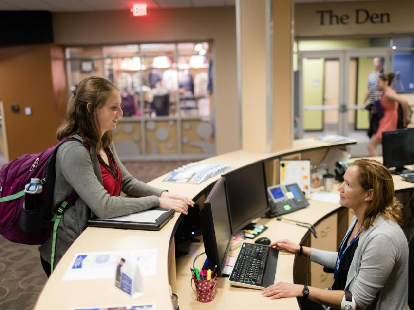 Student stands at the front desk of the Wausau Campus, as she talks to a staff member