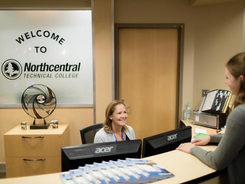 Student talking to a staff member at the front desk of the NTC Wausau Campus.