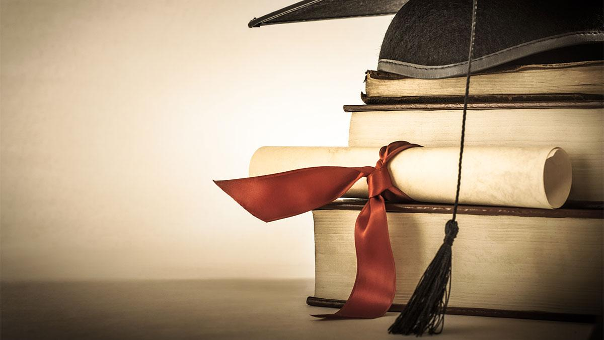 A graduation hat sits on top of three large books and a rolled up paper wrapped in a red bow