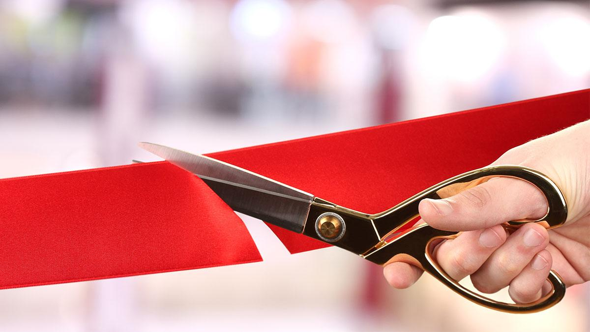 A hand is holding a pair of scissors cutting a large red ribbon