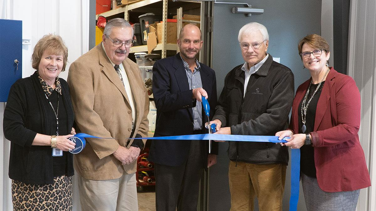 Dr. Weyers stands with four people cutting a grand opening ribbon