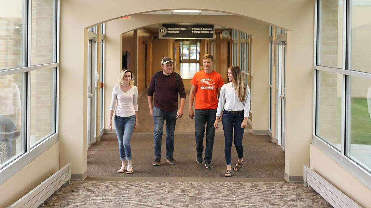 Four students walking down the hallway together