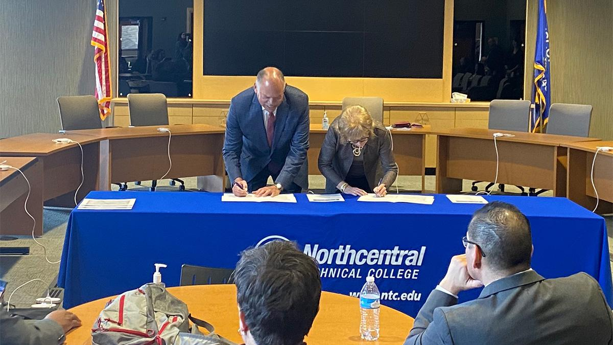 Dr. Lori Weyers stands with Dr. Jack E. Daniels, III signing the official partnership agreement for Liberal Art Transfer Associate Degree at NTC