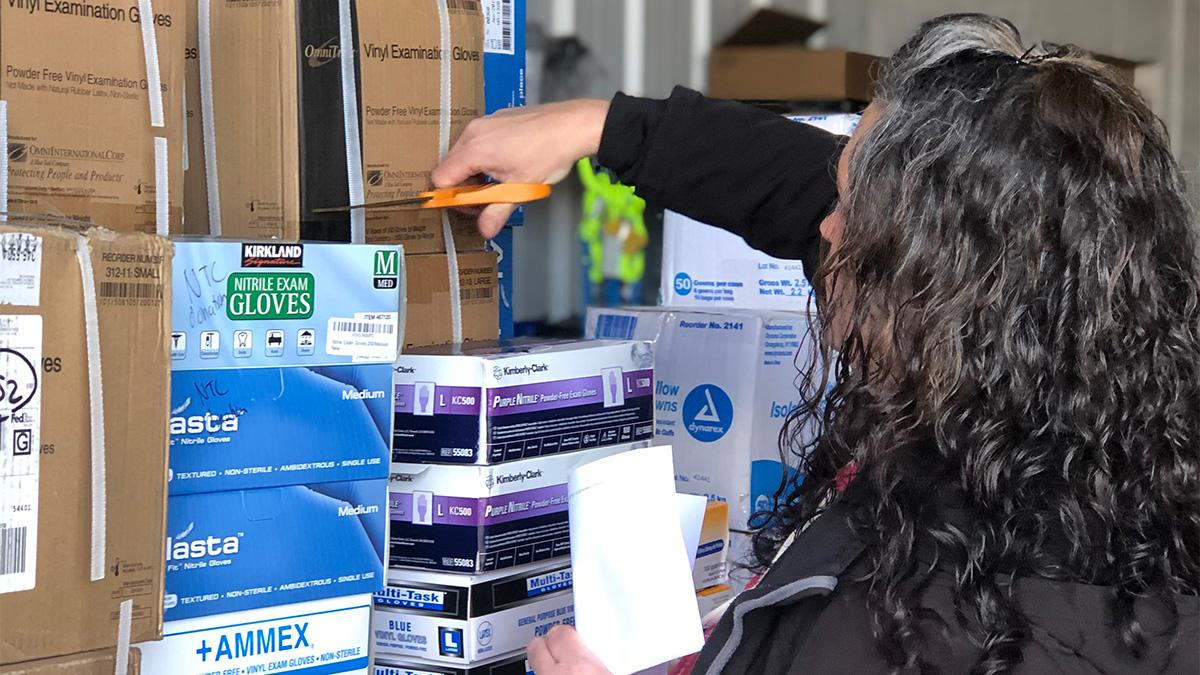 An NTC employee is sorting through various medical supplies
