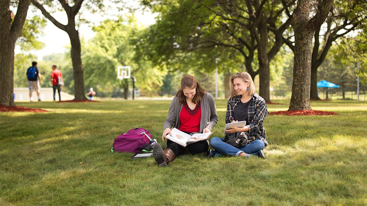 Two students sit together on the grass with school books in the Wausau Campus Courtyard